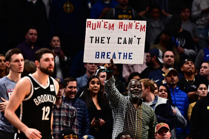 General view as a Denver Nuggets fan holds up a sign in reference to the elevation inside the Pepsi Center during the fourth quarter Brooklyn Nets.