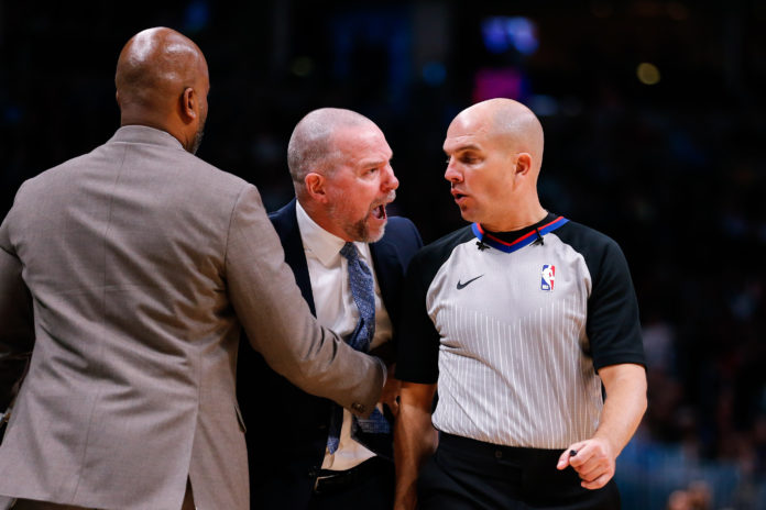 Denver Nuggets head coach Michael Malone (C) argues a call with referee Jaclyn Goble (R) as assistant coach Wes Unseld Jr. (L) holds him back in the fourth quarter against the Houston Rockets at the Pepsi Center