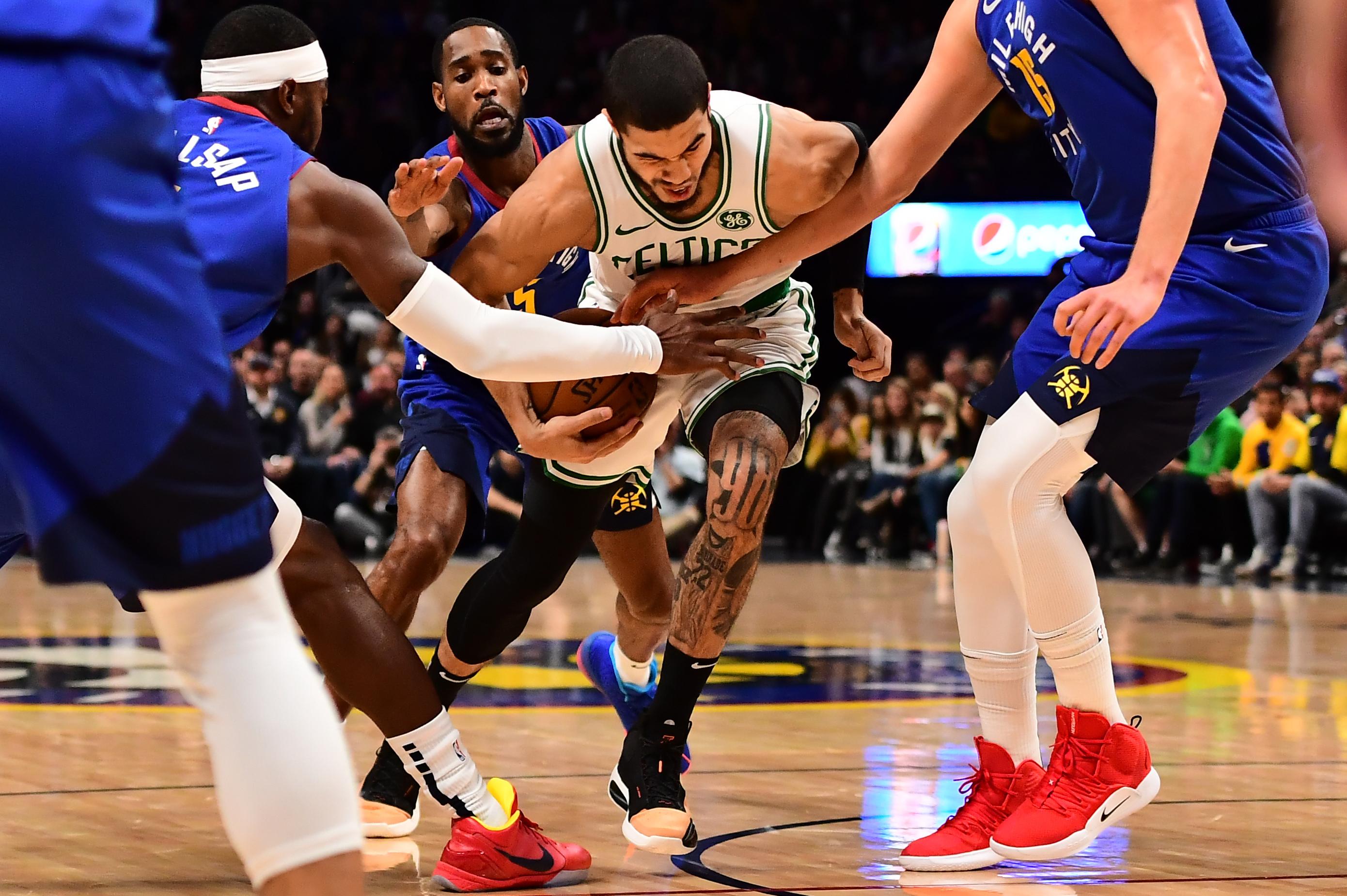 Denver Nuggets forward Paul Millsap (4) and guard Will Barton (5) and center Nikola Jokic (15) reach in on Boston Celtics forward Jayson Tatum (0) in the first quarter at the Pepsi Center.