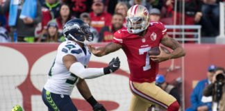 Colin Kaepernick stiff-arms Bobby Wagner in Jan. 2017. Credit: Kyle Terada, USA TODAY Sports.