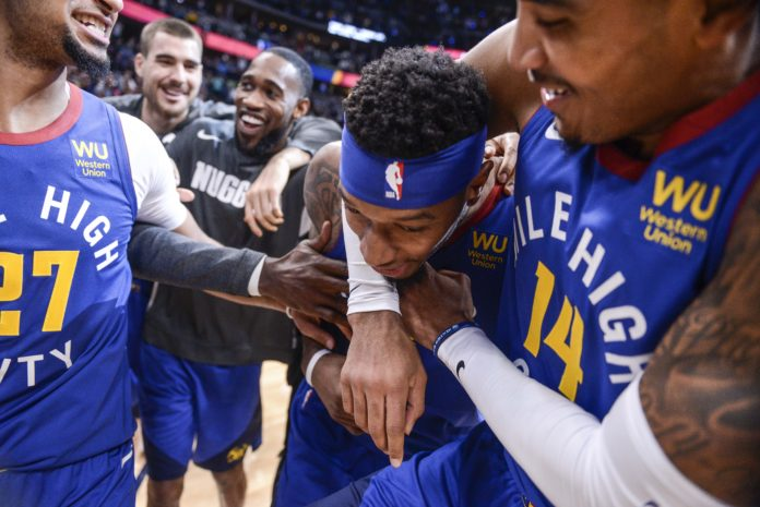Denver Nuggets guard Gary Harris (14) hugs forward Torrey Craig (3), who blocked a shot to win the game against the Phoenix Suns in overtime at Pepsi Center.
