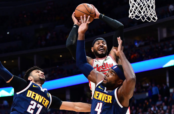 Portland Trail Blazers forward Carmelo Anthony (00) pulls a rebound away from Denver Nuggets guard Jamal Murray (27) and forward Paul Millsap (4) in the first quarter at the Pepsi Center.