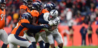 Denver Broncos inside linebacker Todd Davis (51) and cornerback Isaac Yiadom (26) and linebacker A.J. Johnson (45) tackle Oakland Raiders running back DeAndre Washington (33) in the second half at Empower Field at Mile High.