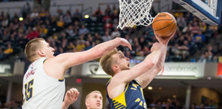 Denver Nuggets center Nikola Jokic (15) fouls Indiana Pacers forward Domantas Sabonis (11) while shooting in the second half at Bankers Life Fieldhouse.