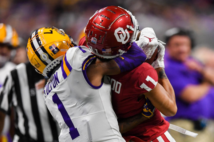 LSU Tigers cornerback Kristian Fulton (1) defends Oklahoma Sooners wide receiver Jadon Haselwood (11) on a catch during the fourth quarter of the 2019 Peach Bowl college football playoff semifinal game at Mercedes-Benz Stadium.