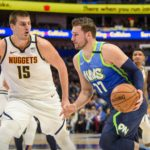 Dallas Mavericks forward Luka Doncic (77) drives to the basket past Denver Nuggets center Nikola Jokic (15) during the first quarter at the American Airlines Center.