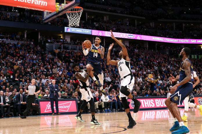 Denver Nuggets guard Gary Harris (14) drives to the net against Los Angeles Clippers guard Patrick Beverley (21) and forward Maurice Harkless (8) in the second quarter at the Pepsi Center.