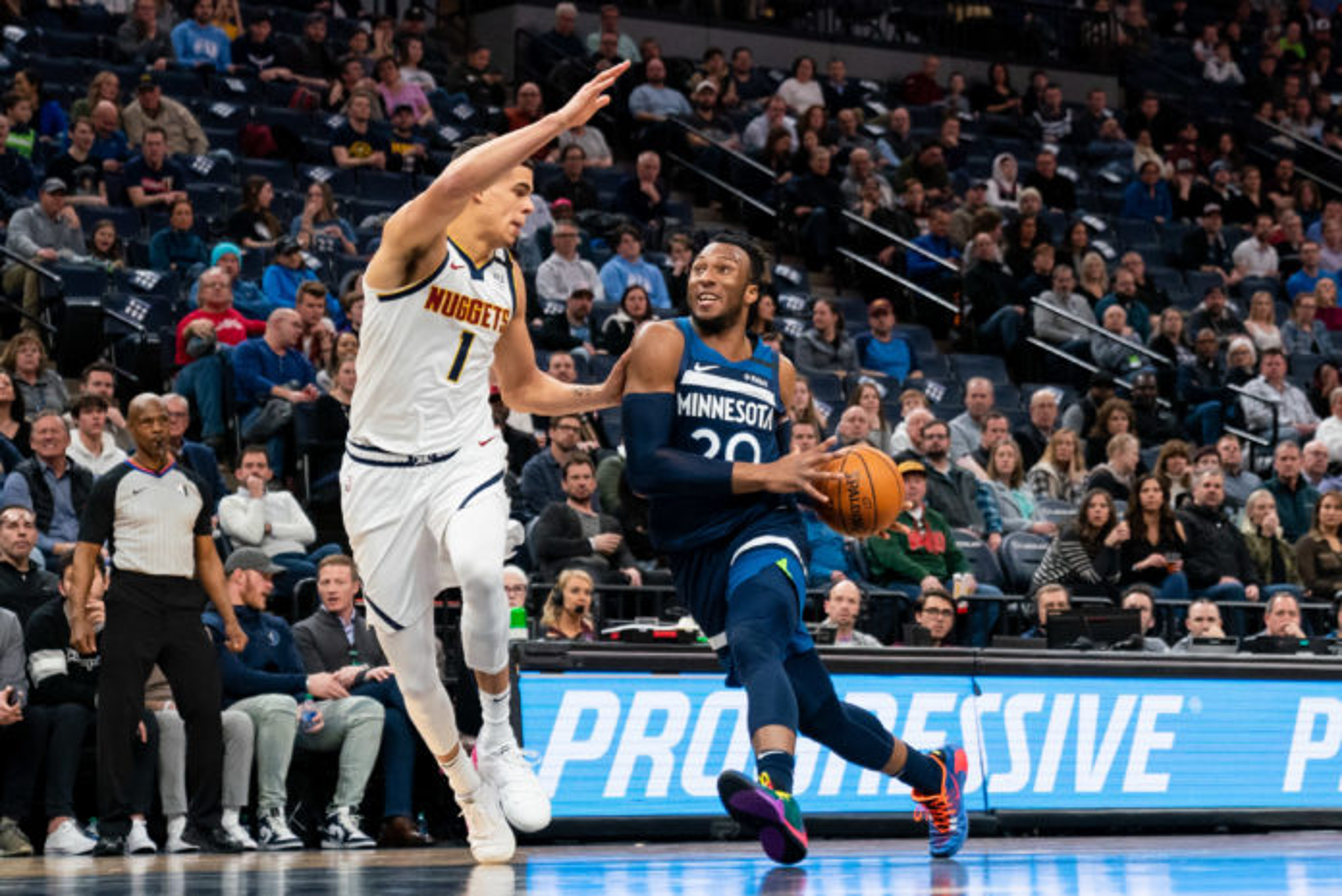 Minnesota Timberwolves guard Josh Okogie (20) dribbles in the third quarter against Denver Nuggets forward Michael Porter Jr. (1) at Target Center.
