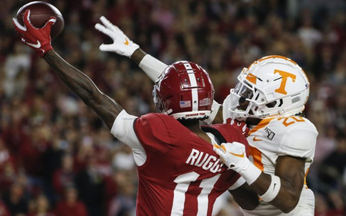 Henry Ruggs catches a pass with a defender draped on his back. Credit: Butch Dill, USA TODAY Sports.