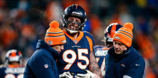 Denver Broncos defensive end Derek Wolfe (95) is helped off the field in the fourth quarter against the Los Angeles Chargers at Empower Field at Mile High.