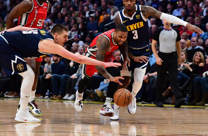 Nuggets center Nikola Jokic (15) reaches in on Portland Trail Blazers guard Damian Lillard (0) as forward Torrey Craig (3) chases from behind in the second half at Pepsi Center. Mandatory Credit: Ron Chenoy-USA TODAY Sports