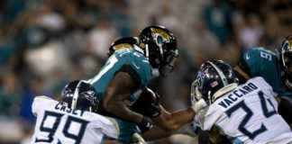 Jacksonville Jaguars running back Leonard Fournette (27) runs the ball as Tennessee Titans defensive end Jurrell Casey (99) defends during the fourth quarter at TIAA Bank Field.