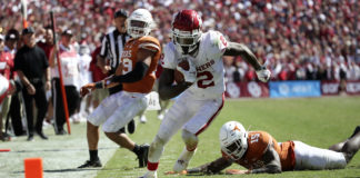 Oklahoma Sooners wide receiver CeeDee Lamb (2) runs over Texas Longhorns defensive back Chris Brown (15) and scores a touchdown during the second half at the Cotton Bowl.
