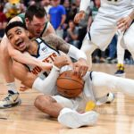 Milwaukee Bucks guard Pat Connaughton (24) reaches for the ball over the back of Denver Nuggets guard Gary Harris (14) in the first quarter at the Pepsi Center.