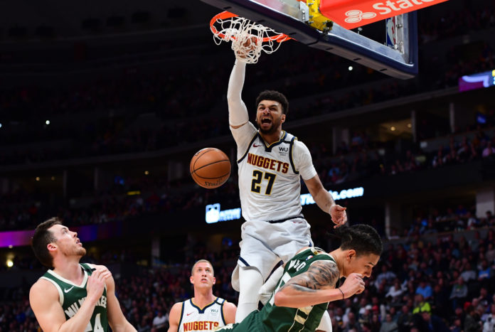 Denver, Colorado, USA; Denver Nuggets guard Jamal Murray (27) finishes off a basket over Milwaukee Bucks forward D.J. Wilson (5) in the third quarter at the Pepsi Center.