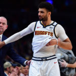 Denver Nuggets guard Jamal Murray (27) and head coach Michael Malone celebrate defeating the Milwaukee Bucks at the Pepsi Center.