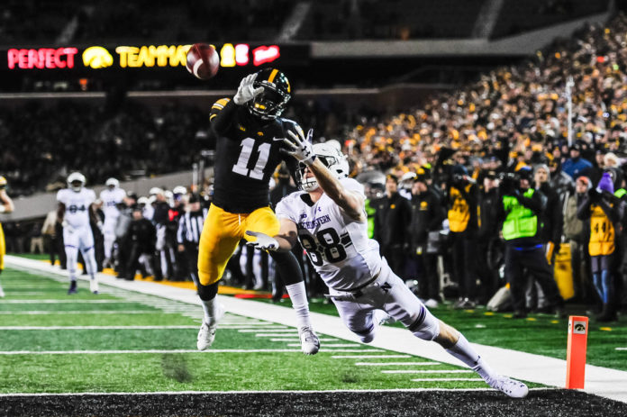 Northwestern Wildcats wide receiver Bennett Skowronek (88) reaches for a touchdown catch as Iowa Hawkeyes defensive back Michael Ojemudia (11) defends during the fourth quarter at Kinnick Stadium.