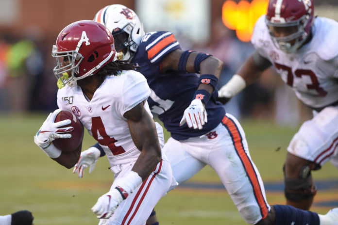Alabama Crimson Tide wide receiver Jerry Jeudy (4) runs the ball ahead of Auburn Tigers defensive back Smoke Monday (21) during the second quarter at Jordan-Hare Stadium.