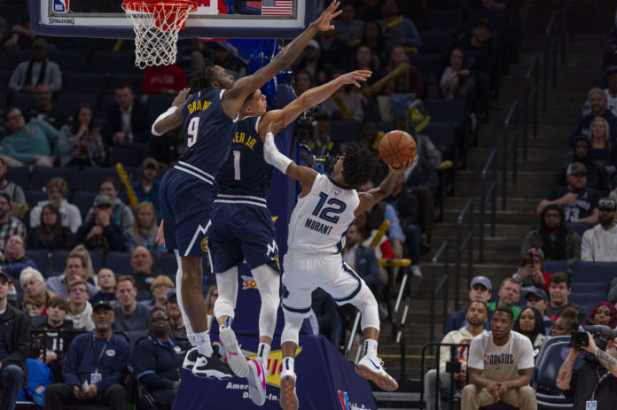 Memphis Grizzlies guard Ja Morant (12) goes to the basket against Denver Nuggets forward Michael Porter Jr. (1) during the second half at FedExForum.