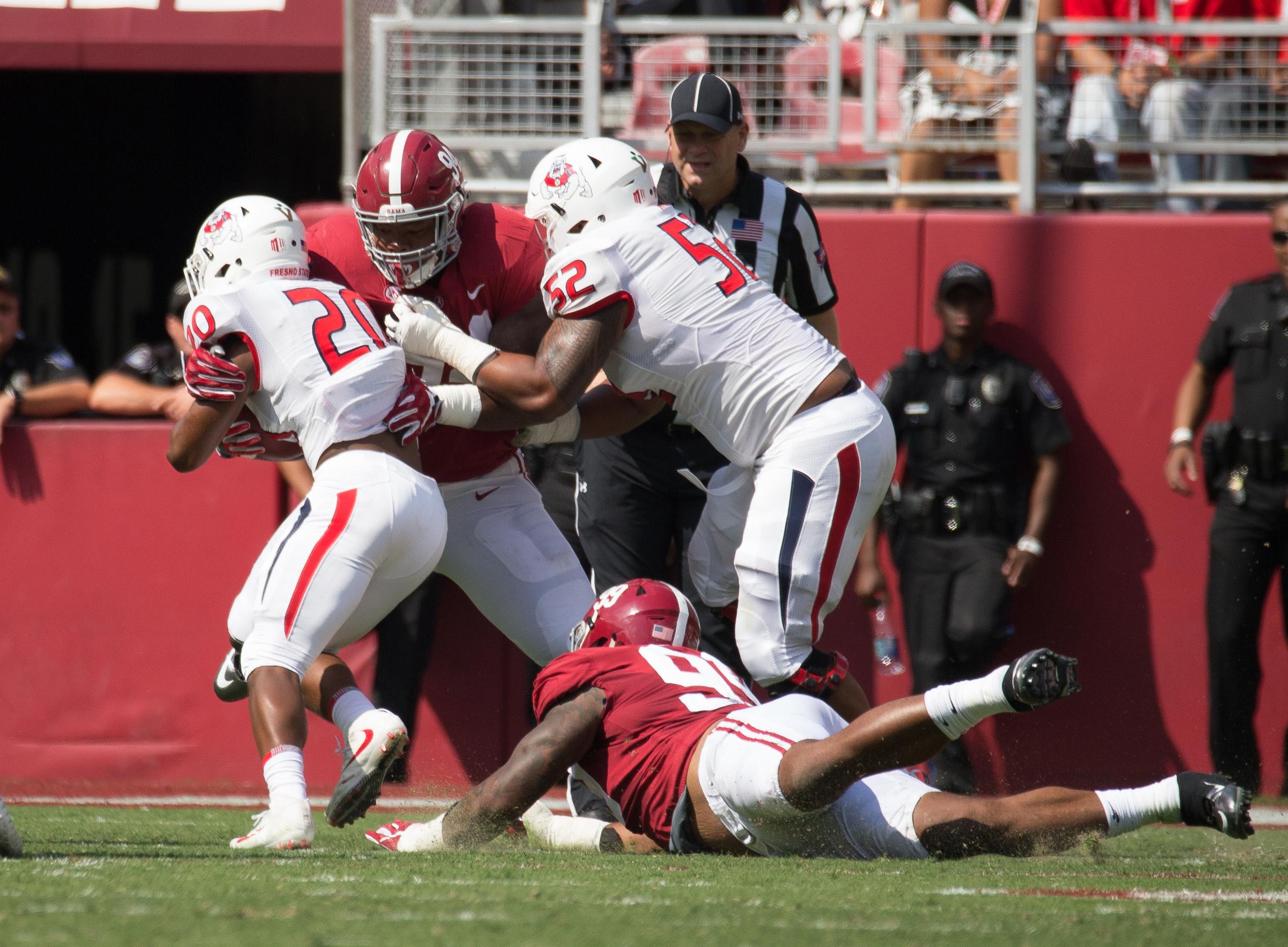 Alabama Crimson Tide defensive lineman Da'Ron Payne (94) is blocked by Fresno State Bulldogs offensive lineman Netane Muti (52) as he tackles Fresno State Bulldogs running back Ronnie Rivers (20) at Bryant-Denny Stadium.