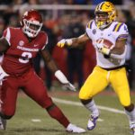 LSU Tigers running back Nick Brossette (4) rushes as Arkansas Razorbacks defensive lineman McTelvin Agim (3) defends in the first quarter at Donald W. Reynolds Razorback Stadium.