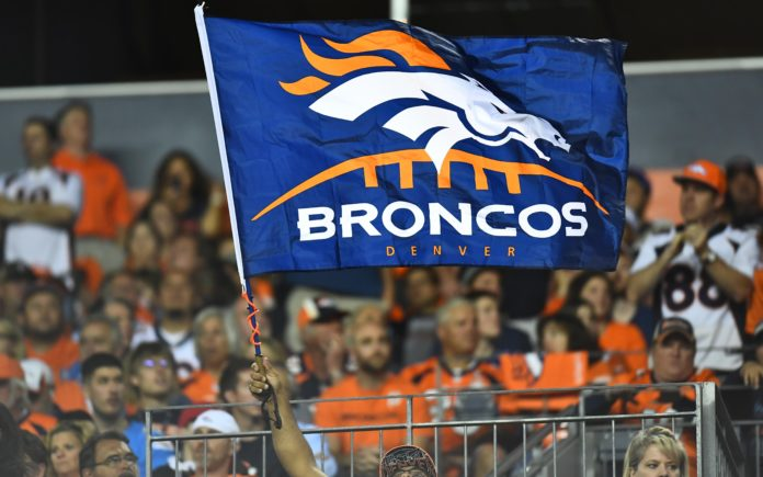 Broncos fans fly a flag. Credit: Ron Chenoy, USA TODAY Sports.