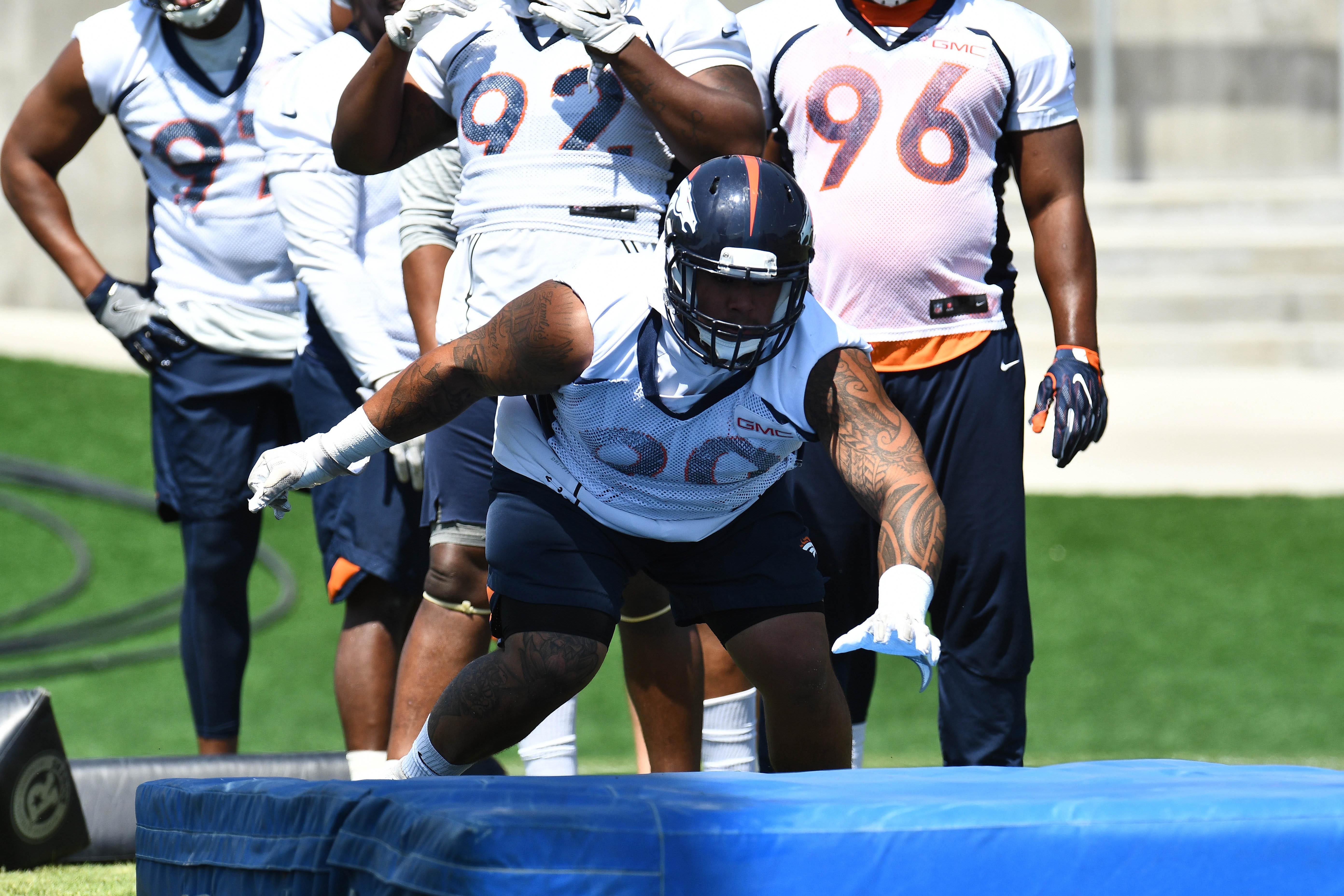Denver Broncos nose tackle Kyle Peko (90) dives during mini camp drills at the UCHealth Training Center.