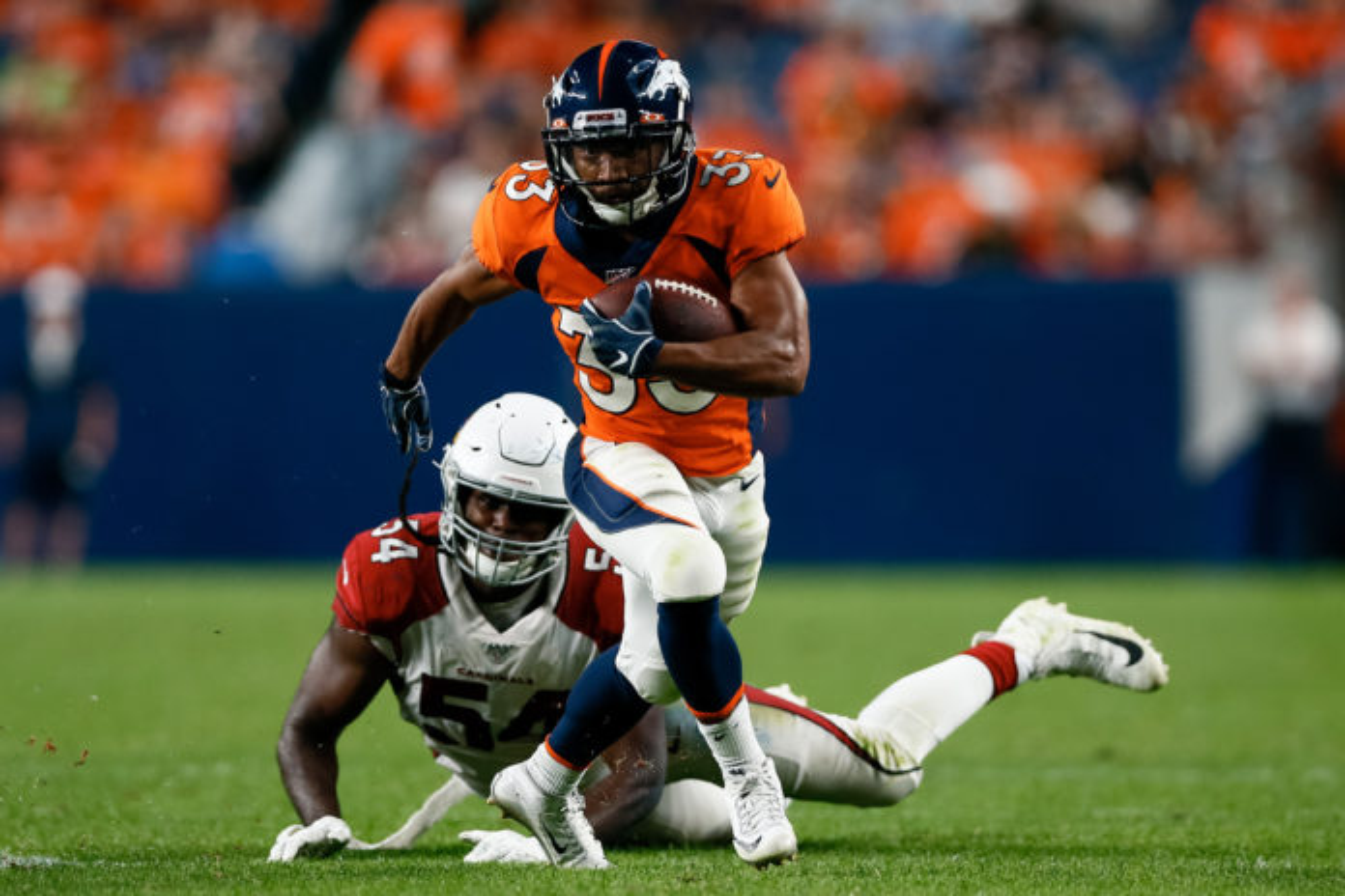 Denver Broncos running back Khalfani Muhammad (33) runs through the tackle of Arizona Cardinals linebacker Vontarrius Dora (54) in the fourth quarter at Broncos Stadium at Mile High.