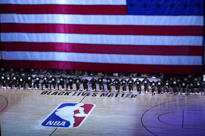 Members of the Orlando Magic and Brooklyn Nets kneel around a Black Lives Matter logo during the national anthem before the start of an NBA basketball game.