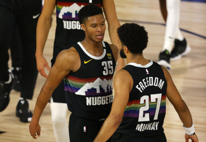 Jamal Murray #27 of the Denver Nuggets and PJ Dozier #35 of the Denver Nuggets react after their win over Utah Jazz in game five of the first round of the 2020 NBA Playoffs at ESPN Wide World of Sports Complex.