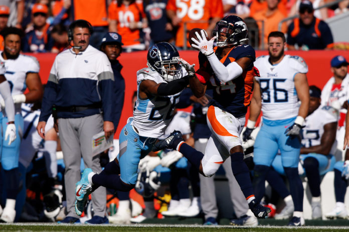 Denver Broncos wide receiver Courtland Sutton (14) makes a catch under pressure from Tennessee Titans cornerback Logan Ryan (26) in the second quarter at Empower Field at Mile High. Mandatory Credit
