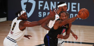 LA Clippers forward Kawhi Leonard (middle) is fouled by Denver Nuggets forward Torrey Craig (right) as he passes the ball against Denver forward Jerami Grant (9) during the first half of game two in the second round of the 2020 NBA Playoffs at AdventHealth Arena.