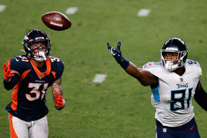 Denver Broncos free safety Justin Simmons (31) attempts to grab a pass intended for Tennessee Titans tight end Jonnu Smith (81) in the third quarter at Empower Field at Mile High.