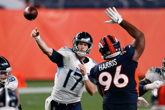 Tennessee Titans quarterback Ryan Tannehill (17) passes as Denver Broncos defensive end Shelby Harris (96) attempts to block in the fourth quarter at Empower Field at Mile High.