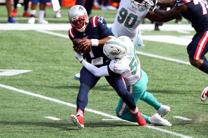 Miami Dolphins outside linebacker Jerome Baker (55) sacks New England Patriots quarterback Cam Newton (1) during the first quarter at Gillette Stadium.