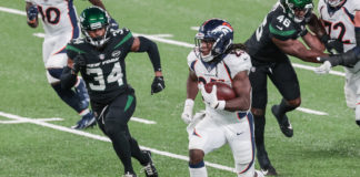 Denver Broncos running back Melvin Gordon (25) carries the ball as New York Jets cornerback Brian Poole (34) pursues during the second half at MetLife Stadium.