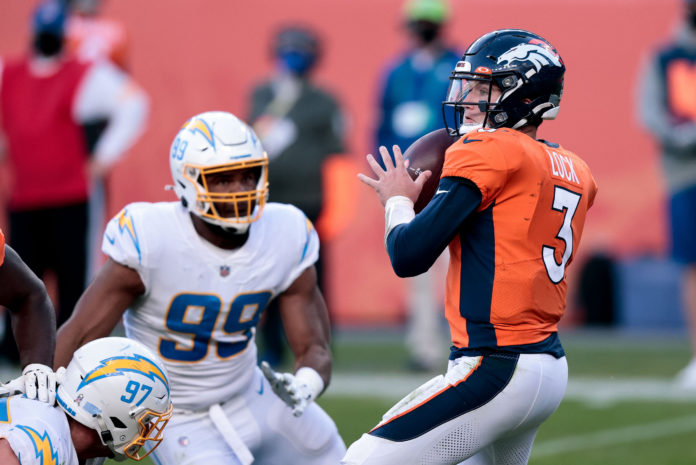 Denver Broncos quarterback Drew Lock (3) looks to pass under pressure from Los Angeles Chargers defensive tackle Jerry Tillery (99) in the third quarter at Empower Field at Mile High