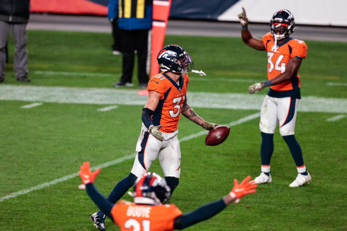 Denver Broncos safety Justin Simmons (31) celebrates his interception against the Miami Dolphins as cornerback A.J. Bouye (21) and cornerback Essang Bassey (34) react in the fourth quarter at Empower Field at Mile High.