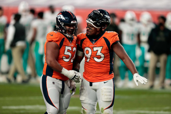 Denver Broncos guard Netane Muti (52) and defensive end Dre'Mont Jones (93) talk during a timeout in the fourth quarter against the Miami Dolphins at Empower Field at Mile High.