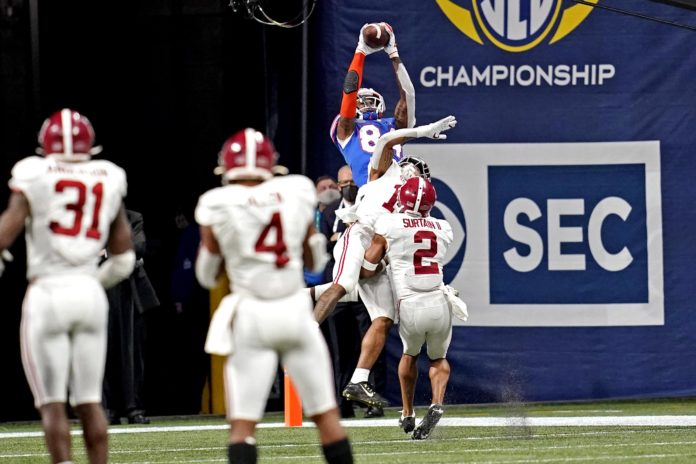 Florida Gators tight end Kyle Pitts (84) makes a touchdown catch against Alabama Crimson Tide defensive back Patrick Surtain II (2) during the fourth quarter in the SEC Championship at Mercedes-Benz Stadium.