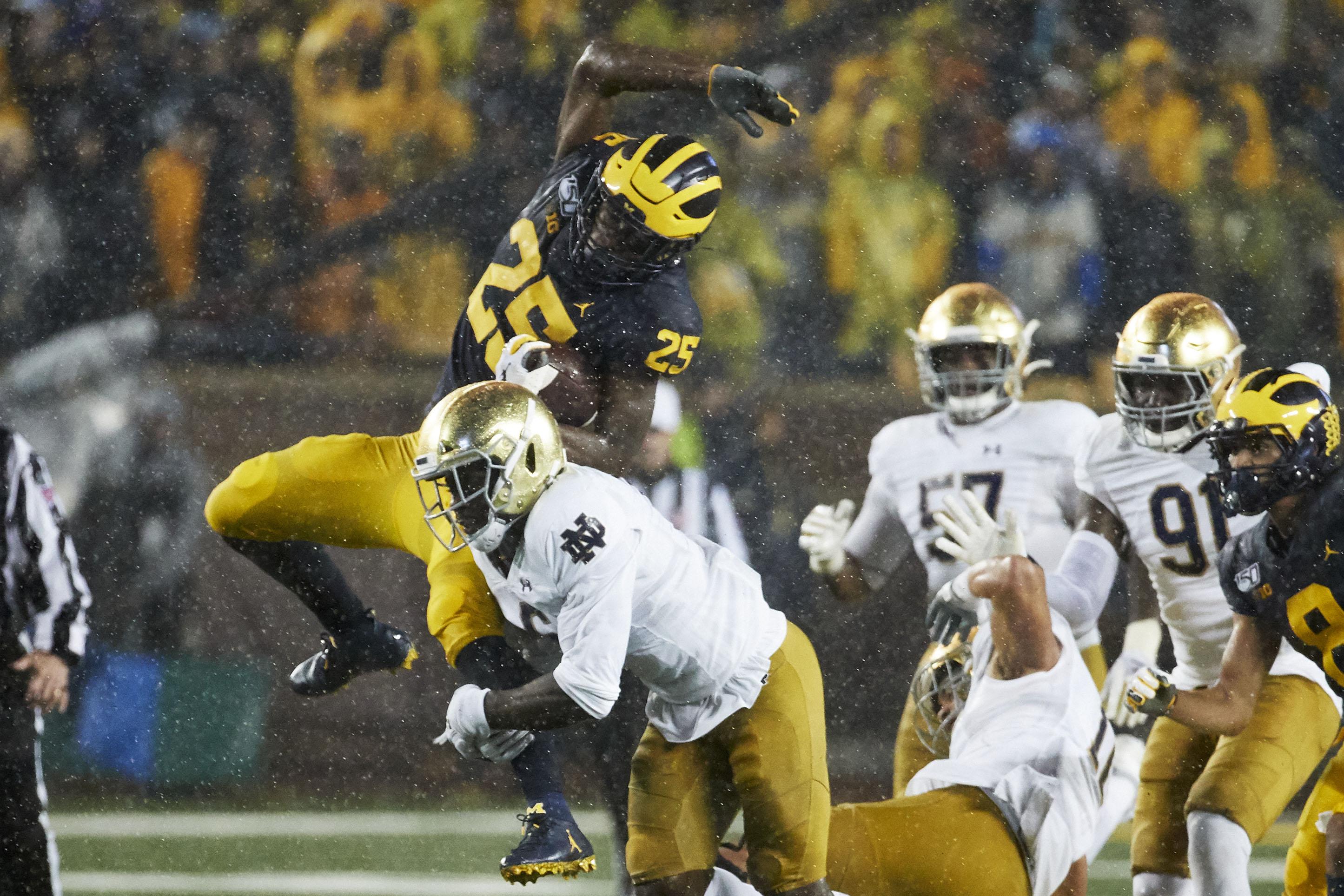 Michigan Wolverines running back Hassan Haskins (25) leaps over Notre Dame Fighting Irish linebacker Jeremiah Owusu-Koramoah (6) in the first half at Michigan Stadium.
