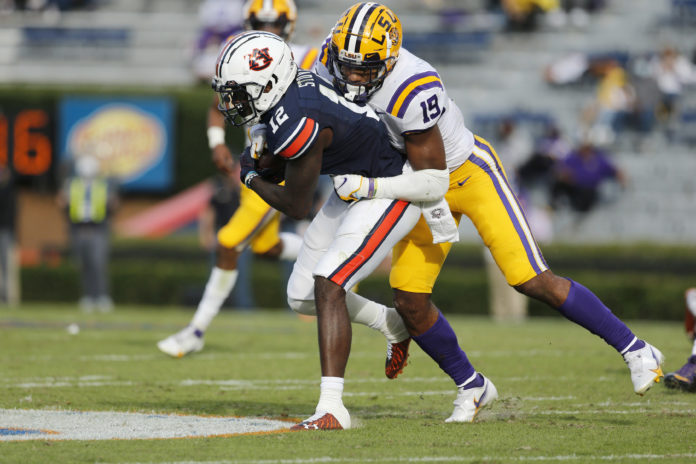 Auburn Tigers receiver Eli Stove (12) is tackled by LSU Tigers linebacker Jabril Cox (21) during the second quarter at Jordan-Hare Stadium.