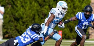 Javonte Williams runs through tackles, like he's known to do. Credit: Jim Dedmon, USA TODAY Sports.