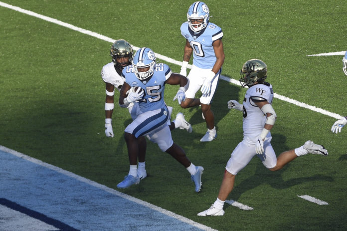 North Carolina Tar Heels running back Javonte Williams (25) scores a touchdown as Wake Forest Demon Deacons defensive backs Caelen Carson (29) and Nick Andersen (45) defend in the fourth quarter at Kenan Memorial Stadium