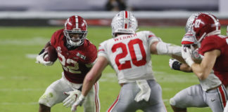 Alabama Crimson Tide running back Najee Harris (22) rushes upfield toward Ohio State Buckeyes linebacker Pete Werner (20) during the second quarter of the College Football Playoff National Championship at Hard Rock Stadium in Miami Gardens, Fla.