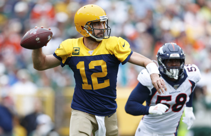 Green Bay Packers quarterback Aaron Rodgers (12) throws a pass under pressure from Denver Broncos linebacker Von Miller (58) during the second quarter at Lambeau Field.