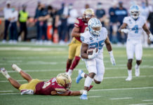 North Carolina Tar Heels running back Javonte Williams (25) avoids the tackle of Boston College Eagles Sam Johnson III (14) and scores a 41-yard receiving touchdown during the second quarter at Alumni Stadium.