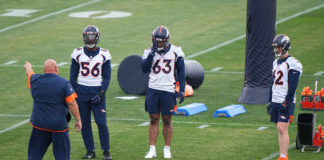 Denver Broncos linebacker Baron Browning (56) and inside linebacker Curtis Robinson( 63) and inside linebacker David Curry (62) listen to linebackers coach Reggie Herring during rookie minicamp at the UCHealth Training Center.