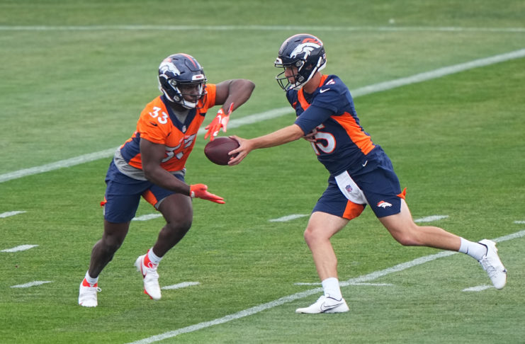 Denver Broncos quarterback Case Cookus (15) hands the ball off to running back Javonte Williams (33) during rookie minicamp at the UCHealth Training Center.