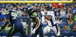 Denver Broncos quarterback Teddy Bridgewater (5) scrambles out of the pocket to pass against the Seattle Seahawks during the first quarter at Lumen Field.